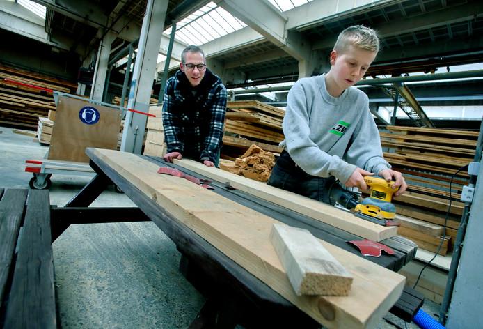 Johan Kolbeek van Zwijndrecht Werkt begeleidt een leerling van praktijkschool De Sprong bij het schaven en schuren.