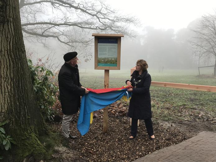 Wethouder Joosten en burgemeester Raven onthullen het bord bij de begraafplaats.