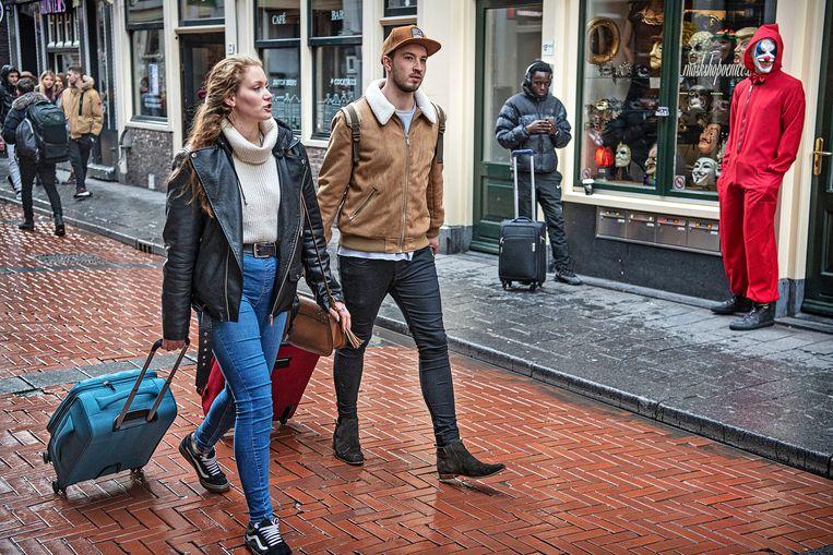 Toeristen met hun onafscheidelijke rolkoffers lopen over de Warmoestraat richting hotel. Beeld Guus Dubbelman / de Volkskrant