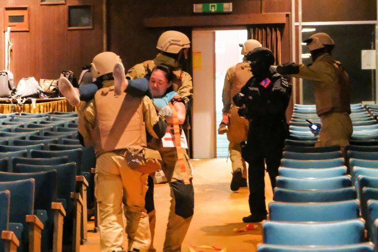 Het eliteteam van de brandweer evacueert slachtoffers tijdens een oefening, nauw samenwerkend met het interventieteam van de politie.