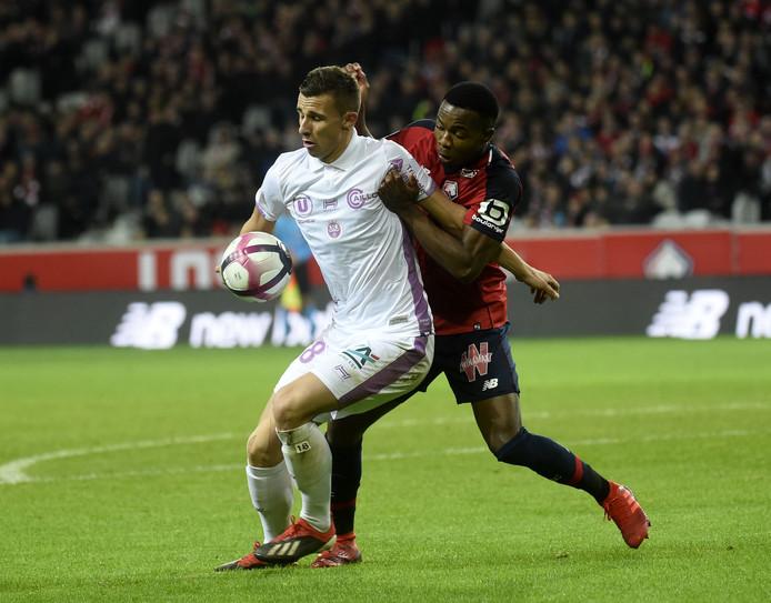 Een duel tussen een speler van Lille en een speler van Stade Reims.