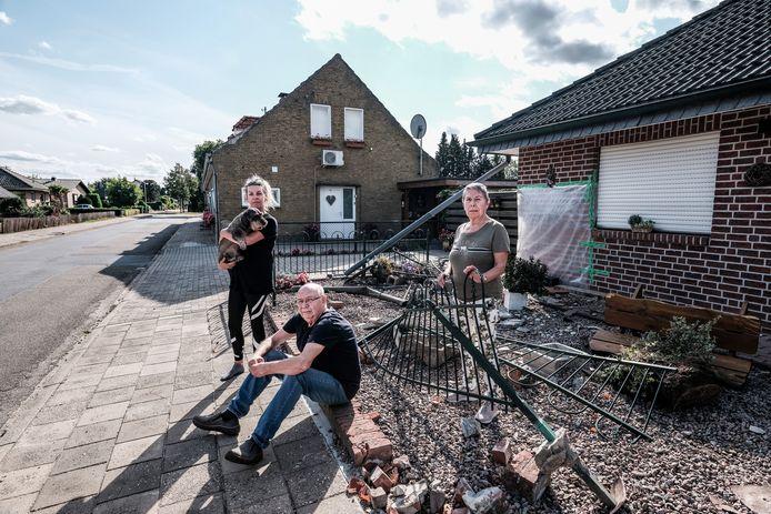 De familie Buil in hun vernielde tuin, waar een aanhanger crashte.  Foto : Jan Ruland van den Brink