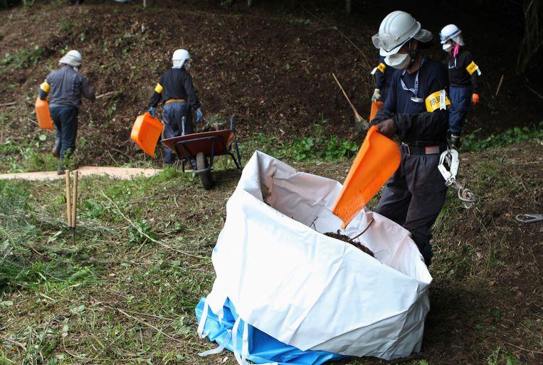 Arbeiders verwijderen besmette grond en bladeren in Fukushima. Volgens de Japanse wet mogen jongeren onder 18 niet werken in radioactieve gebieden.