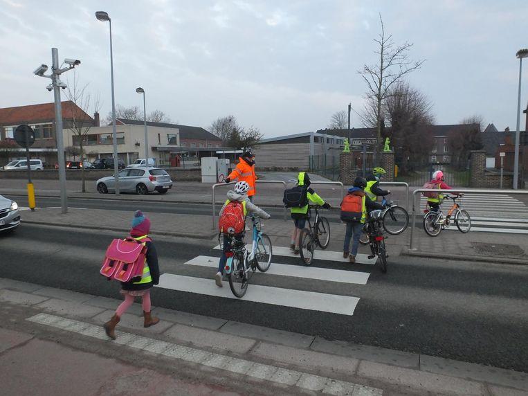 De kinderen steken de Staatsbaan in Zulte over met behulp van de gemachtigd opzichter.