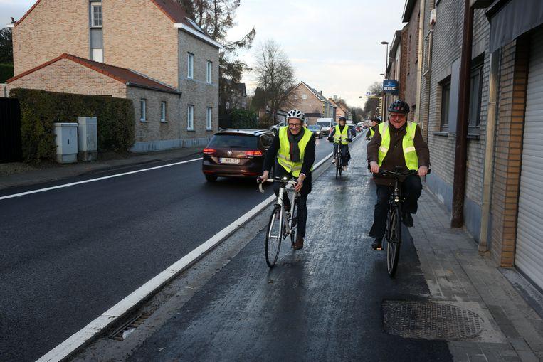 Vlaams minister Ben Weyts (N-VA) en burgemeester Hugo Vandaele (CD&V) fietsen het vernieuwde fietspad op de Alsembergsesteenweg in.