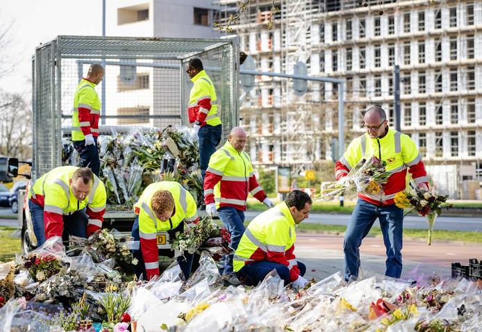 Medewerkers van de gemeente verzamelen de bloemen die na de aanslag op het 24 Oktoberplein werden neergelegd.