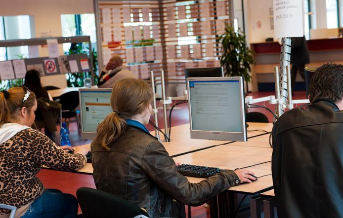 Een jonge vrouw bekijkt vacatures bij het UWV Werkplein.