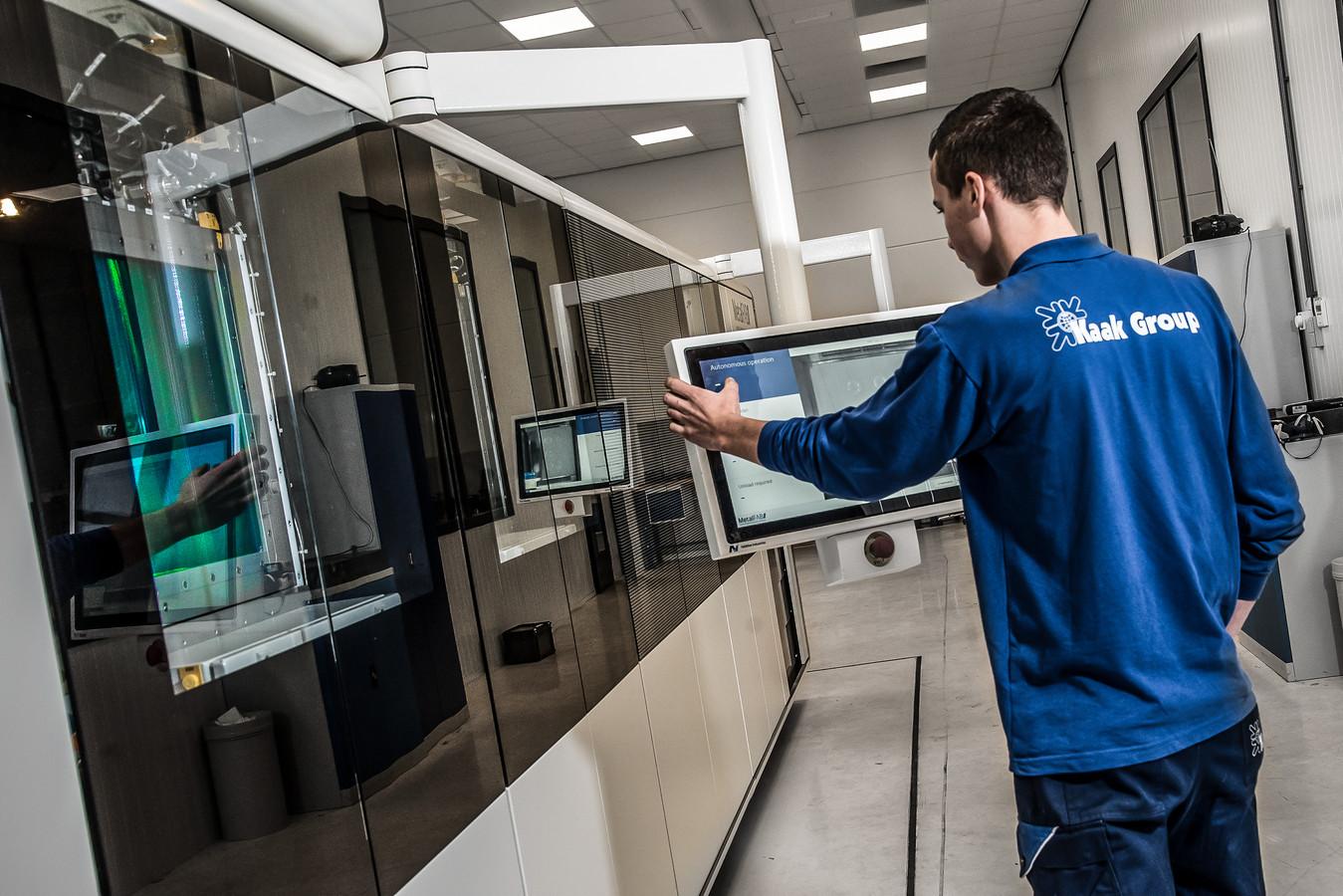 Een werknemer van Kaak Group aan het werk met een 3D metaalprinter van Additive Industries in Eindhoven.