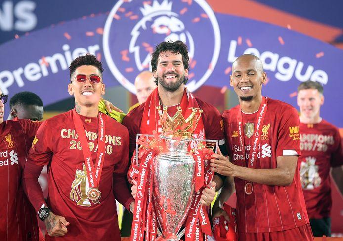 Fabinho (rechts) met Roberto Firmino (links) en Alisson Becker met de trofee van de Premier League