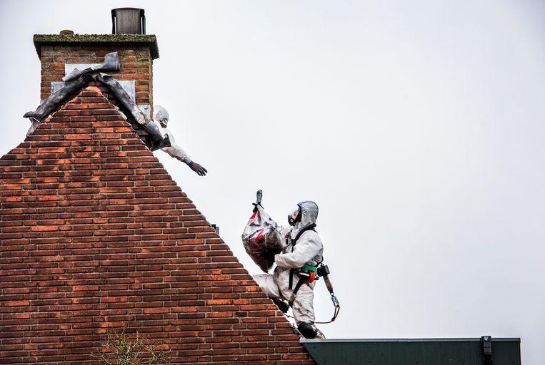 Asbestverwijdering van een dak in Wateringen. Beeld Raymond Rutting / De Volkskrant