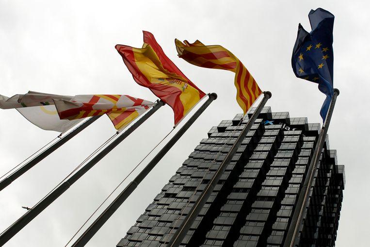 Vlaggen voor het hoofdkantoor van La Caixa in Barcelona, de grootste spaarbank in Spanje (Reuters) Beeld REUTERS