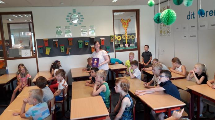 Fauve Hendrickx laat de kinderen uit haar klas het boekje zien dat ze zojuist van wethouder Jan van Hal heeft gekregen.