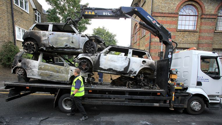 Uitgebrande auto's worden weggehaald uit de Londense wijk Hackney daags na de rellen. Beeld getty
