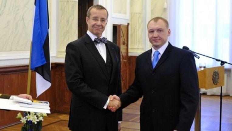 De Estlandse veiligheidsofficier Eston Kohver (rechts) schudt de hand van president Toomas Hendrik Ilves in 2010. Beeld ap