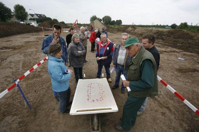 Het voornamelijk uit Kapel-Avezaath afkomstige publiek krijgt uitleg van een archeoloog bij een plattegrond van de oude boerderij. foto Jan Bouwhuis