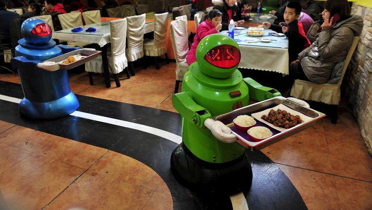Robots serveren gerechten in een robotrestaurant in de Chinese stad Harbin. Wie is er verantwoordelijk als er iets mis gaat? Beeld Reuters