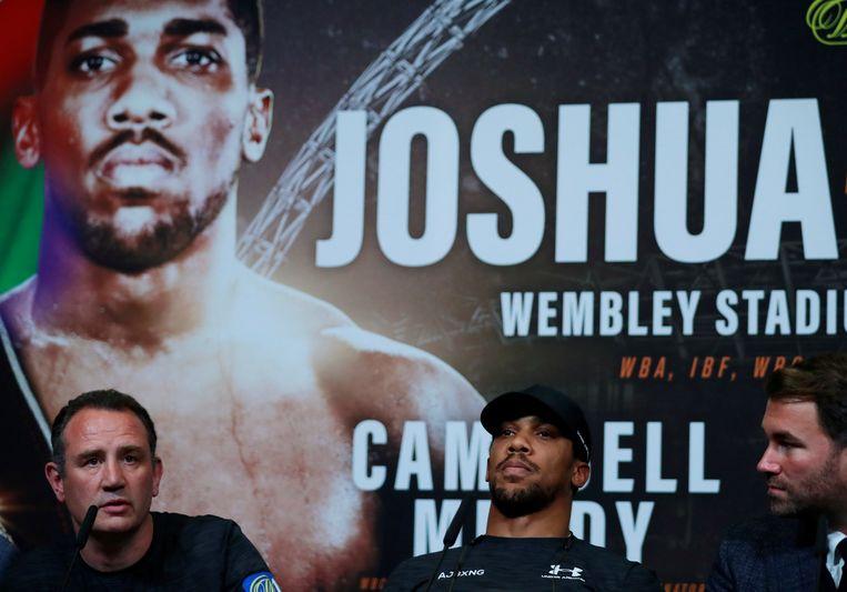 Anthony Joshua met rechts zijn trainer Robert McCracken en bokspromotor Eddie Hearn. Beeld Reuters
