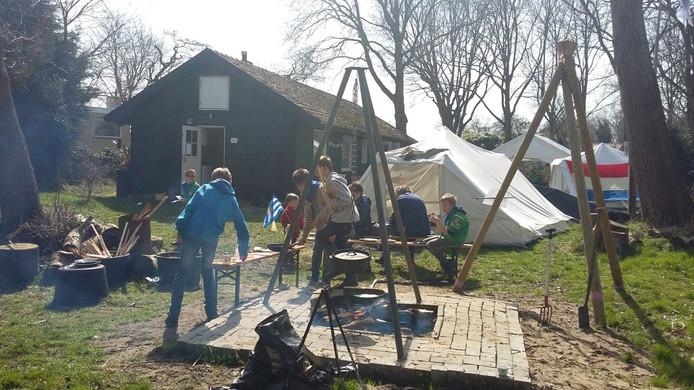 Scouts uit Burgh-Haamstede bakken pannenkoeken op een houtvuur en knopen sleutelhangers tijdens de open dag in 2018.