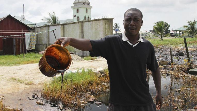 Een visser laat de gevolgen van de olielekkage zien.