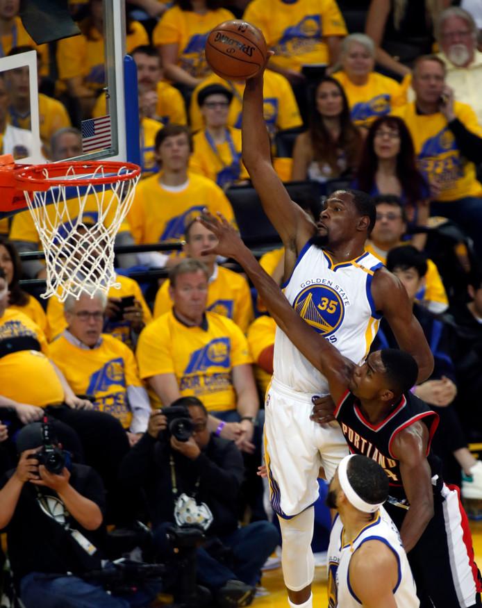 Kevin Durant dunkt de bal over Maurice Harkless van Portland heen.