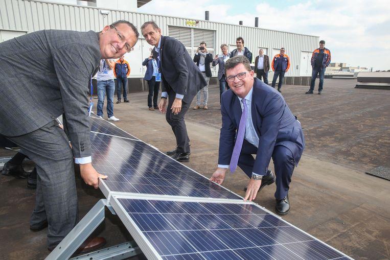 Minister Bart Tommelein legt het eerste zonnepaneel op het dak van Volvo Cars in Gent.