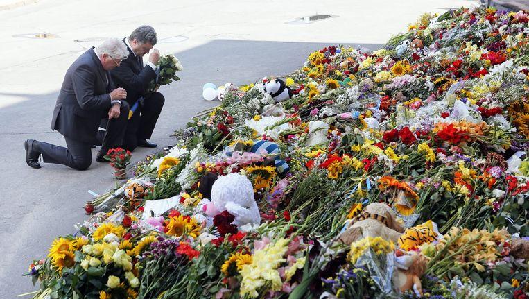 De Oekraiense president Porosjenko (tweede van links) en de Nederlandse ambassadeur in Oekraïne Kees Klomenhouwer leggen bloemen bij de Nederlandse ambassade in Kiev. Beeld epa