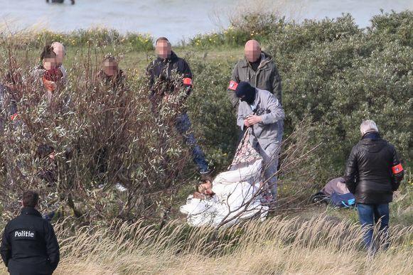 Frank P. toont voor aan de speurders hoe hij z'n moeder (op deze foto een agente, red.) begroef in de duinen.