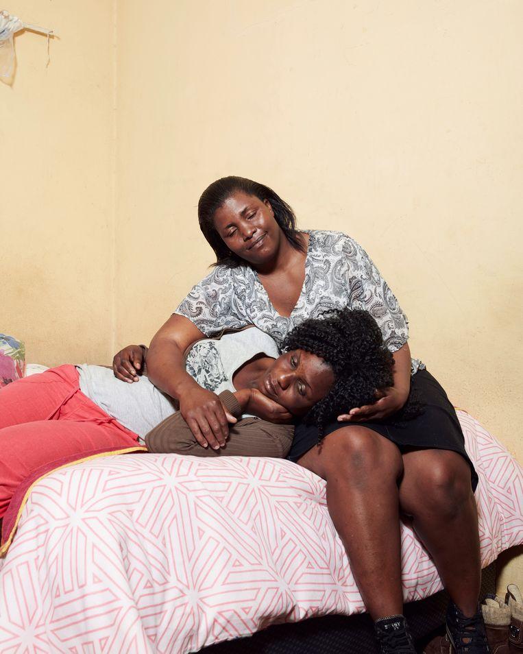 Uit de expositie I will Speak, I will Speak!: Florence (42) en Brilliance (26, liggend) zijn halfzussen uit Zimbabwe, die werken in een seksclub in Johannesburg, Zuid-Afrika. Florence was aanvankelijk bankemployee, Brilliance werkte als schoonmaker. Beiden verloren hun baan en zagen zich gedwongen de prostitutie in te gaan. Florence heeft vijf kinderen in Zimbabwe, die afhankelijk zijn van haar inkomen. Ook andere familieleden worden financieel door haar ondersteund. Brilliance heeft twee dochters, een moeder en een broer die van haar inkomen afhankelijk zijn. Beiden zijn besmet met het hiv-virus.  Beeld Foto Erik Smits