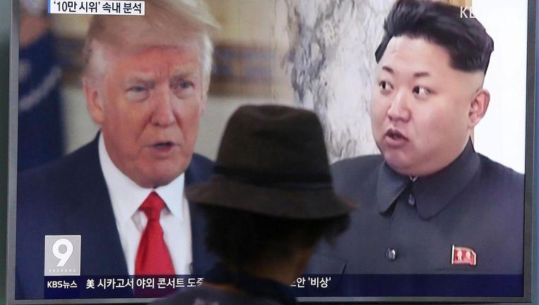 Een man kijkt naar een televisie waarop Donald Trump en Kim Jong Un te zien zijn. Beeld null