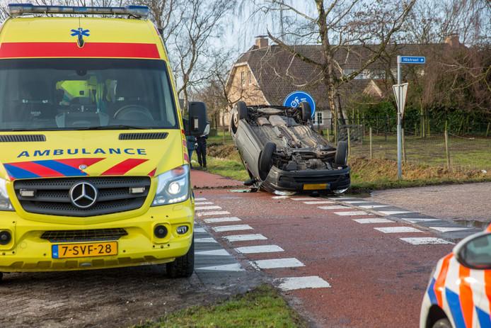 Auto op de kop beland op de Vroenhoutseweg in Roosendaal.
