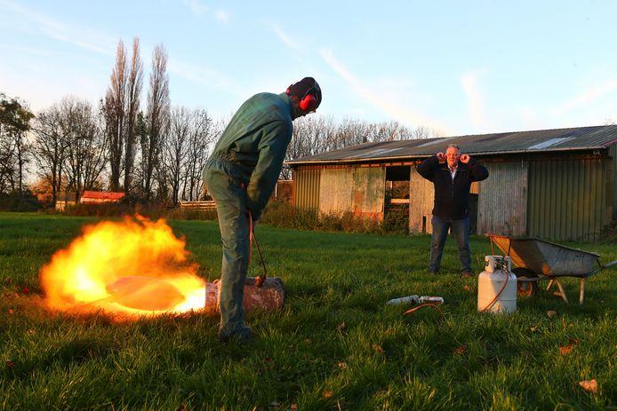 Arno Groeneveld uit Rijswijk schiet zijn boei af, te zien in de vlam. Kees van Vugt steekt zijn vingers in zijn oren.