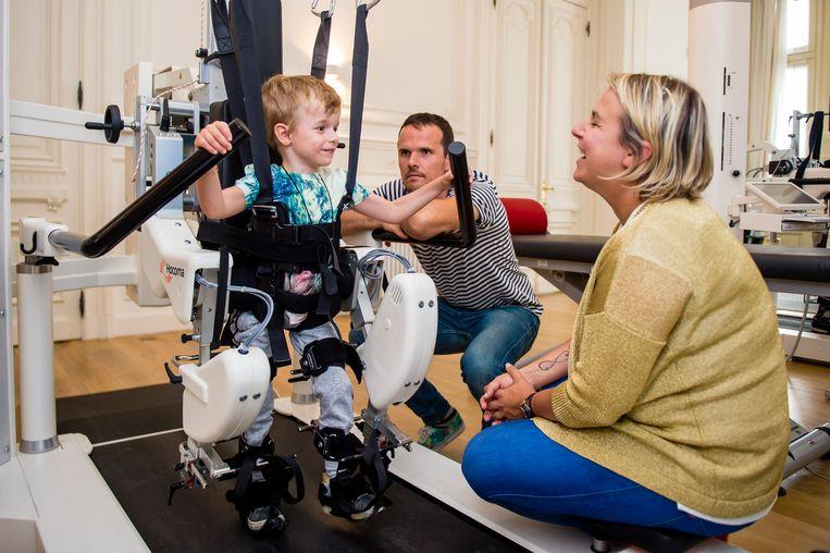 Briek met zijn ouders tijdens een sessie in zijn robotpak.