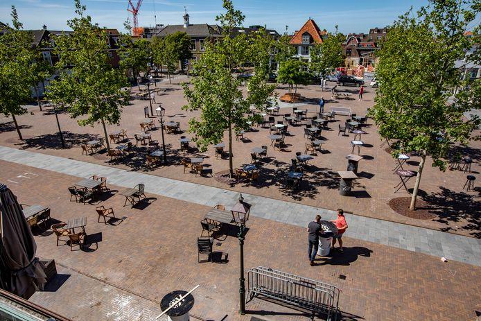 De tafels en stoelen op het Marktplein in 's-Gravenzande worden met anderhalve meter afstand neergezet.