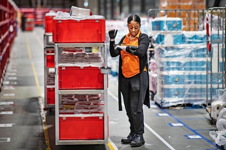 Personeel van Picnic vult de kratten en dozen voor haar online klanten, alles wordt dubbel gescand. Er is veel vraag vanwege het coronavirus. Beeld Guus Dubbelman / de Volkskrant