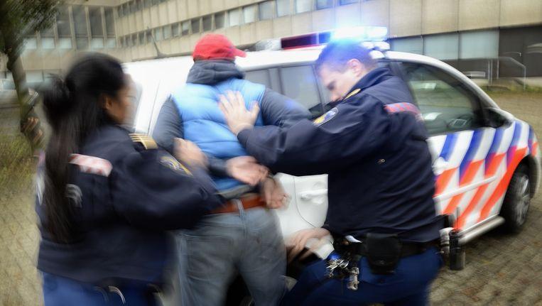 Agenten slaan een arrestant in de boeien. Beeld ANP XTRA Lex van Lieshout
