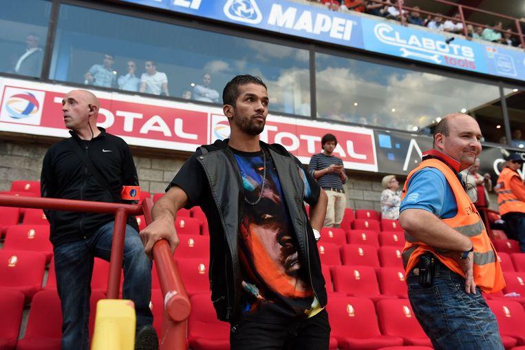 Mehdi Carcela, gekwetst in de tribunes, deed zijn best om de heetgebakerde fans tot bedaren te brengen.