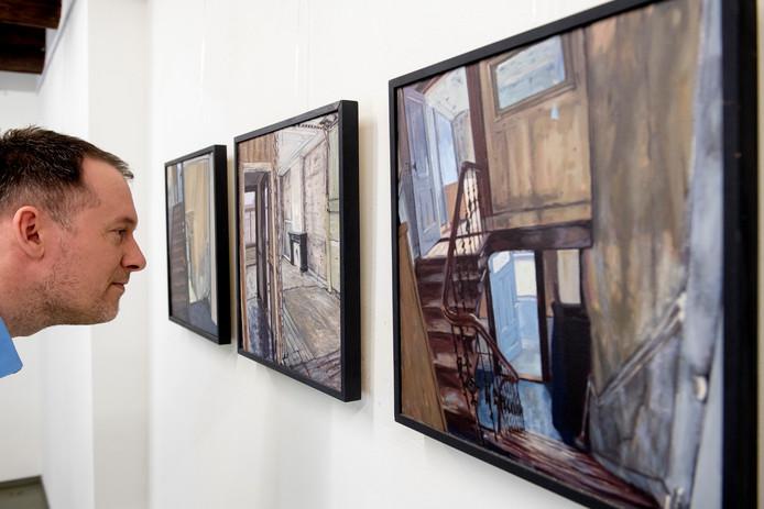 Gijsbert van der Wal bij 3 van de 36 geschilderde interieurs van Paul Gorter in de Waalgalerie.