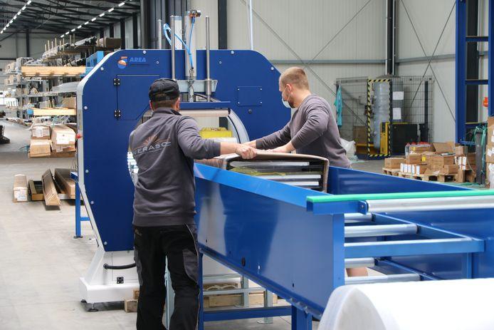Medewerkers van Verasol bij een machine voor het verpakken van veranda's, aan het einde van een nieuwe productielijn die in de Duitse fabriek is geïnstalleerd.