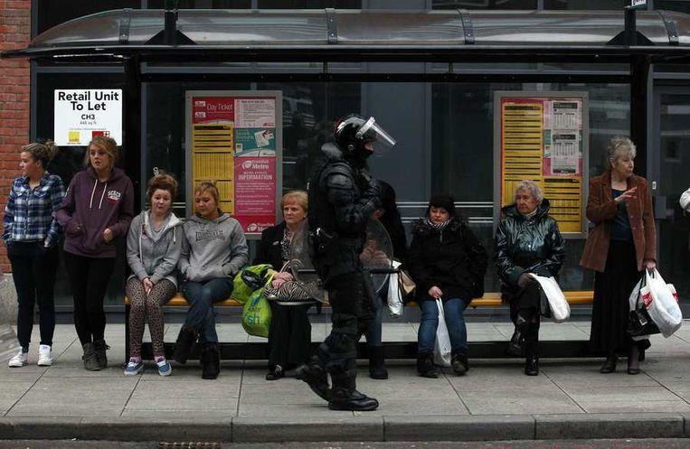 Een lid van de oproerpolitie passeert een bushalte in Belfast, afgelopen zaterdag. Beeld reuters