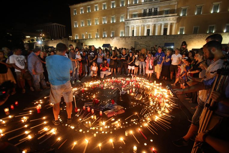 Mensen komen bijeen in Athene om de slachtoffers te herdenken. Beeld EPA