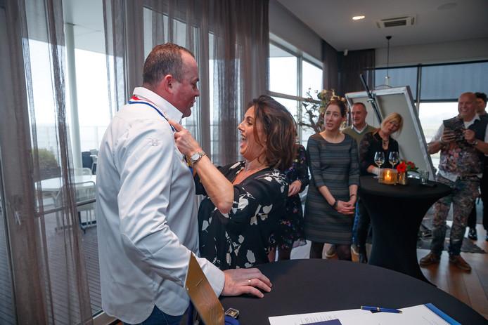Zijn vrouw Ingrid reikt Henrie van der Heijden de koksbuis en de versierselen om.