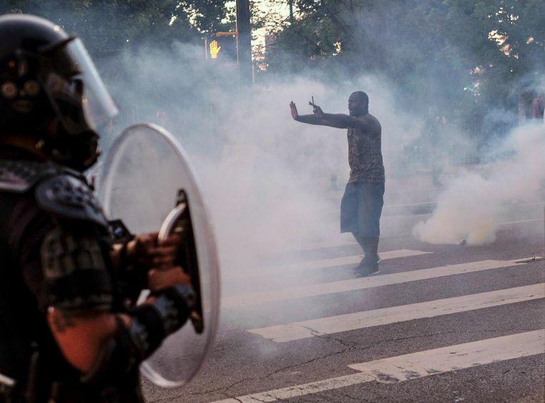 Een man die in Atlanta demonstreert tegen politiegeweld probeert in een wolk van traangas de politie tegen te houden. Volgens Amnesty International schond de politie hiermee op tal van plekken mensenrechten. Beeld AP