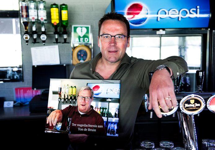 Winand Paulissen, voorzitter van FC Abcoude, met een portret van barman Ton de Bruin, die bezweek aan het coronavirus. Paulissen verloor afgelopen week zelf zijn moeder, die ook door het coronavirus overleed.
