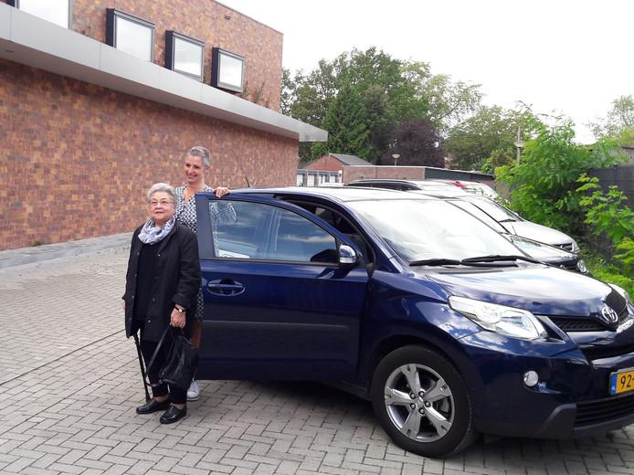 Mevrouw Donna Gehlen-Vetter stapt uit in Helmond met hulp van haar 'taxichauffeur' Nathalie van der Zanden.