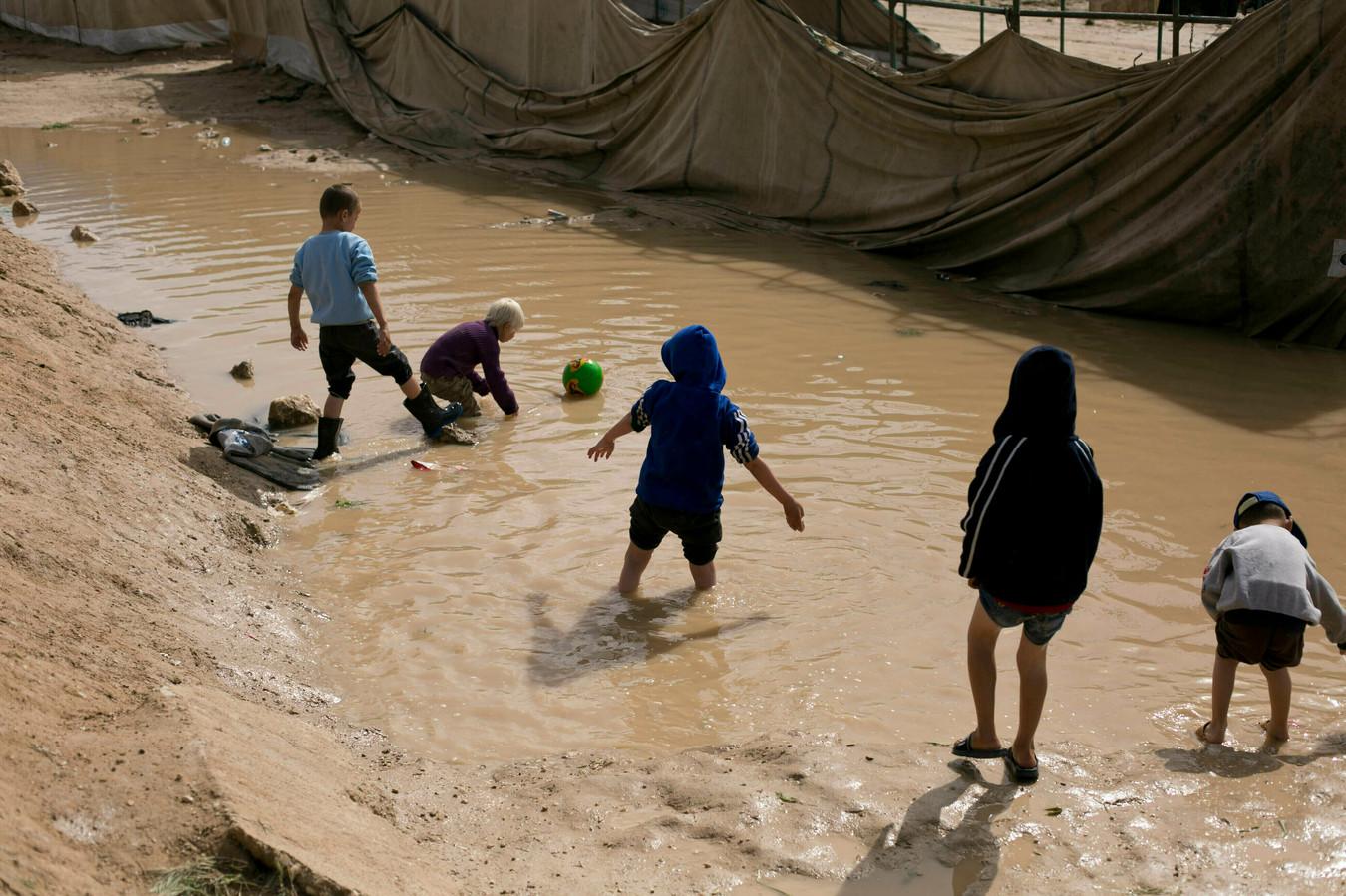 Kinderen spelen in een modderpoel in het Al Hol-kamp in Syrië
