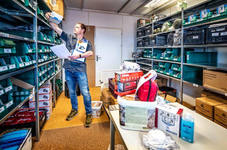 Artikelen vliegen de deur uit bij de prepshop in Utrecht. Jeroen Klaassen helpt met het inpakken van de bestellingen die variëren van mondkapjes tot complete gasmaskers en noodrantsoenen. Beeld Raymond Rutting / de Volkskrant