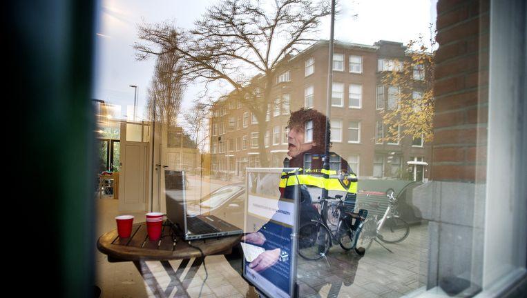 Een agent in een 'pop-up politiebureau' in Rotterdam West. Beeld ANP