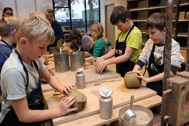 Kinderen boetseren in het atelier beeldjes voor gesneuvelde soldaten.