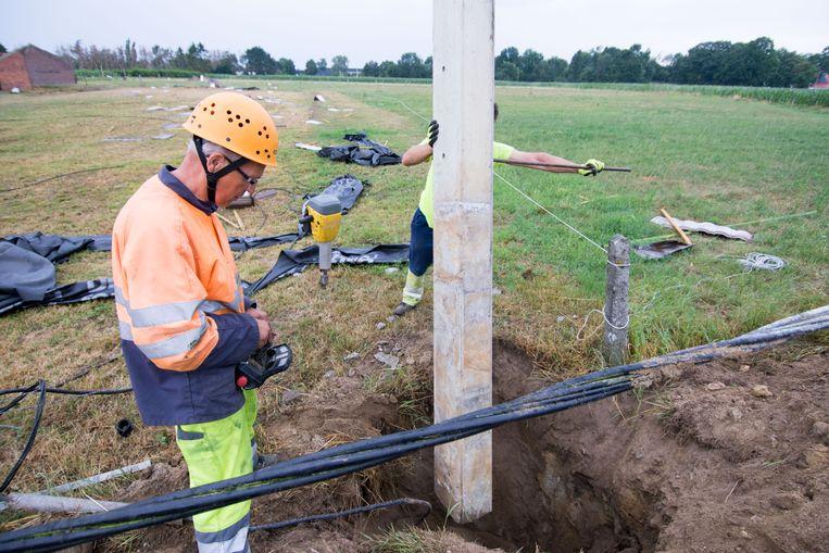Arbeiders plaatsen een nieuwe elektriciteitspaal. De buurt zat daardoor even zonder stroom.
