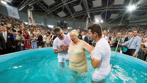 Jehova's treden op volwassen leeftijd toe via een toetredingsritueel van volledige onderdompeling. Foto: een massabijeenkomst in de Poolse stad Lodz, foto uit 2012.